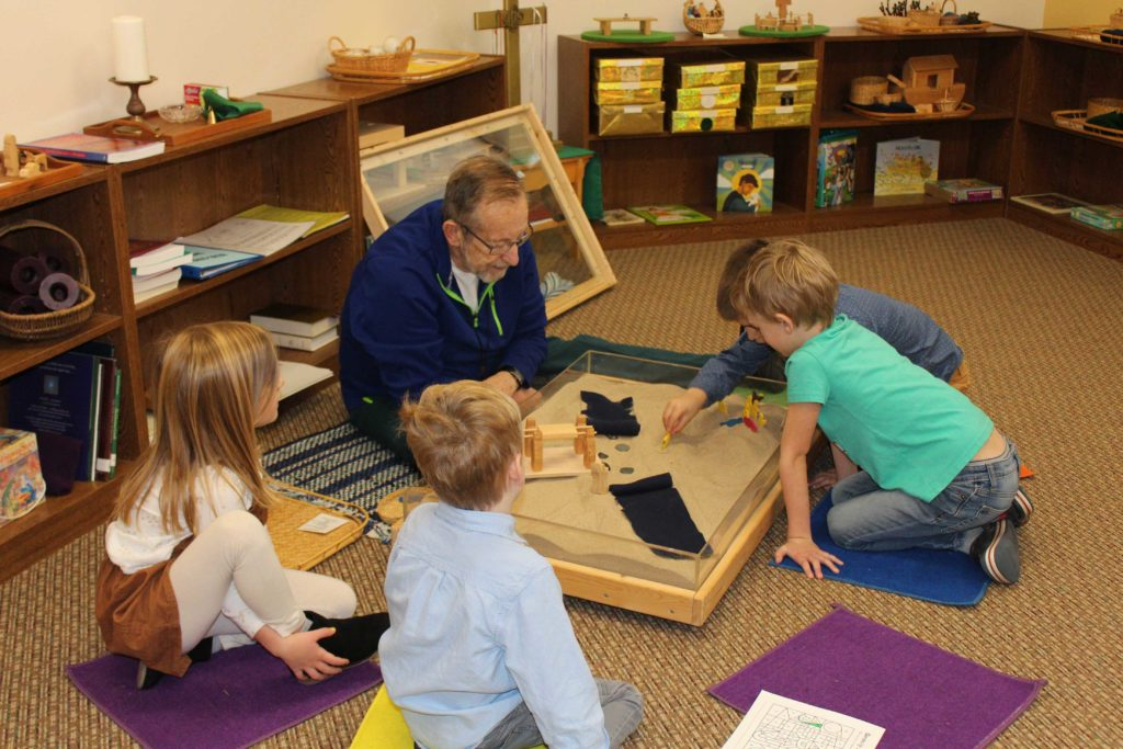 Children setting-up scripture scene in sandbox in Worship Center