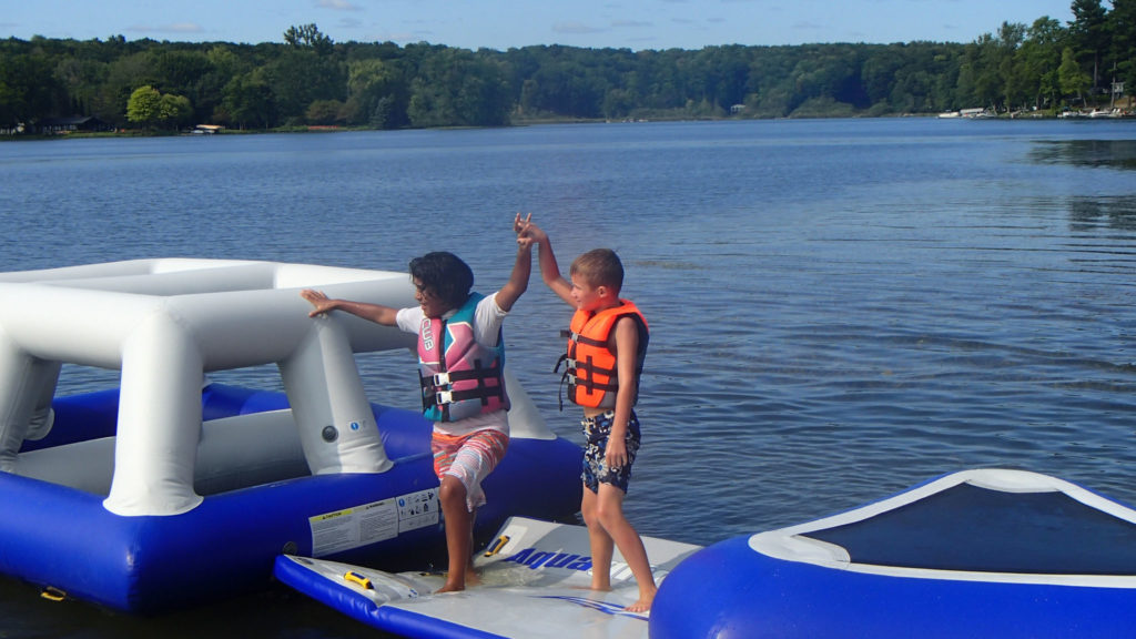 Kids on floating apparatus at Camp Henry