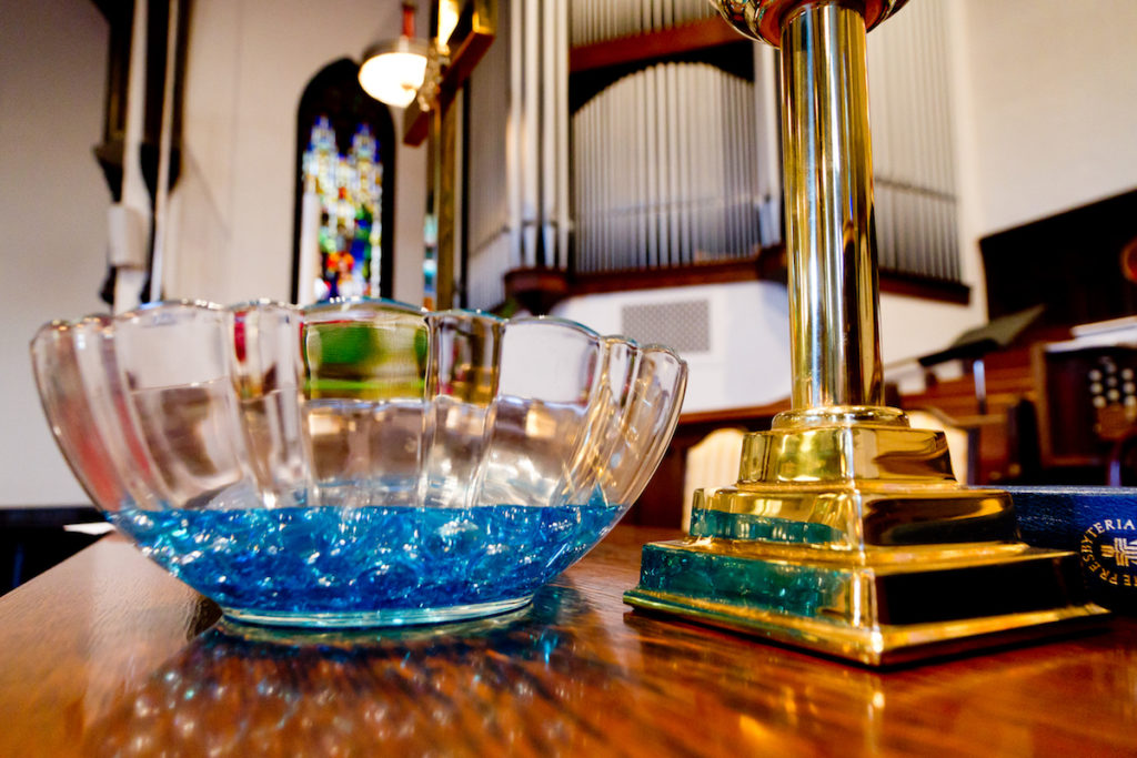 Up close of glass baptismal font and brass cross
