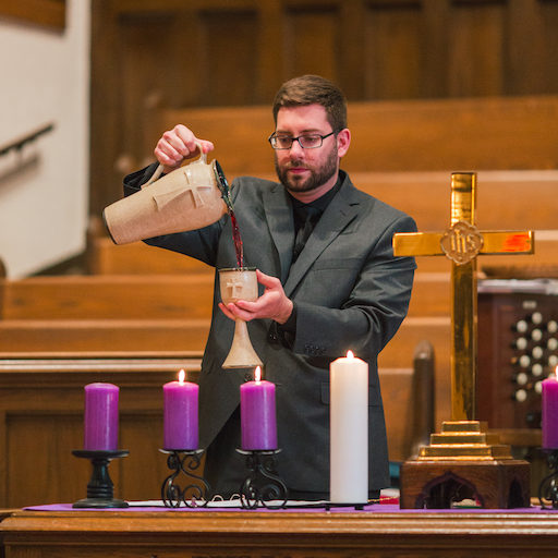 Kyle pouring communion cup
