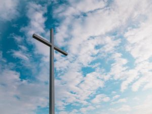 Very tall cross against a blue sky with mottled clouds